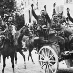THE GERMAN INVASION OF FRANCE AND LOW COUNTRIES, MAY-JUNE 1940 (HU 1755) A group of German soldiers smile and wave for the camera after hearing the request from France for an Armistice.  The men are riding on horseback or are seated in a horse-drawn open-topped carriage. A small dog can also be seen on the carriage. The original caption states that this photograph was published on 26 June 1940. Copyright: © IWM. Original Source: http://www.iwm.org.uk/collections/item/object/205196418