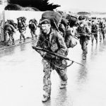 THE FALKLANDS CONFLICT, APRIL - JUNE 1982 (FKD 2815) Heavily laden Royal Marines of 45 Royal Marine Commando, carrying 140lb packs, enter Port Stanley after a remarkable 40 mile march across the Island. Their route from the west coast to the east took them through marshes and mountains, included night time marching and was at that time the longest march in full kit in the history of the Commando force. Copyright: © IWM. Original Source: http://www.iwm.org.uk/collections/item/object/205215330