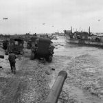 'A' Squadron tanks, having just landed, proceeding along the beaches to the de-waterproofing area, Normandy, 7 June 1944 [Image number: 104776]. Photograph by Major Wilfred Herbert James Sale, MC, 3rd/4th County of London Yeomanry (Sharpshooters), World War Two, North West Europe, 1944.  Landing craft are visible on the shore protected by barrage balloons. Over 4,000 transport vessels (landing ships and landing craft) were used during the landings.  From an album containing 210 photographs compiled by Major W H J Sale, MC, 3rd/4th County of London Yeomanry (Sharpshooters), 1944. National Army Museum Copyright.