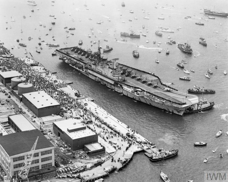 THE FALKLANDS CONFLICT, APRIL - JUNE 1982 (FKD 684) Aerial view of the aircraft carrier HMS HERMES about to berth alongside at Portsmouth Harbour on her return from the Falklands on 21 July 1982.  HERMES is surrounded by small boats which sailed out to welcome her home.  Crowds can also be seen on the quayside. Copyright: © IWM. Original Source: http://www.iwm.org.uk/collections/item/object/205018861