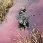THE VIETNAM WAR 1962 - 1975 (CT 164) A US Army radio operator of Blue (Rifle) Platoon Troop B, 1st Sqdn, 9th Cav, 1st Cavalry Division (Air-mobile), moves through purple smoke created by a smoke grenade during an assault mission which formed part of Operation PERSHING in the An Lao Valley, 28 July 1967. The grenade had been dropped by the troop commander from an OH-13 helicopter to mark the area to be checked for Viet Cong supply bun... Copyright: © IWM. Original Source: http://www.iwm.org.uk/collections/item/object/205191134