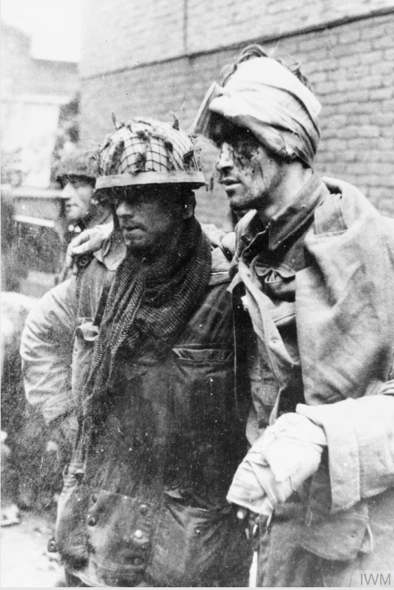 On This Day: 17th September 1944 THE BRITISH AIRBORNE DIVISION AT ARNHEM AND OOSTERBEEK IN HOLLAND  An Allied paratrooper assisting a wounded comrade. This photograph was taken at around 3.30pm east of the Arnhem main road bridge. From left to right. Sapper J Dunney, Sapper C Grier and Lance Corporal R Robb, all of the 1st Parachute Squadron, Royal Engineers. The men had just been shelled and burnt out of the van Lunburgstirum school which they had occupied since the evening of the 17 September. © IWM (HU 2131)