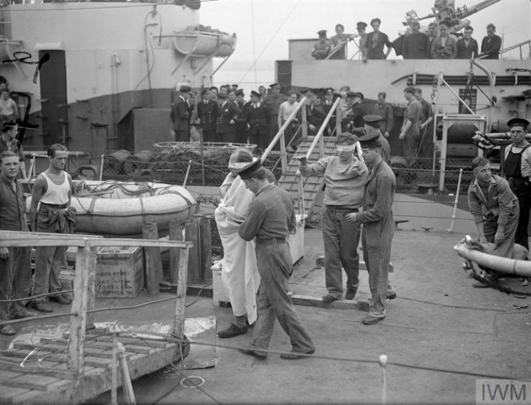 BRITISH NAVAL FORCE SINKS THREE E-BOATS. 19 SEPTEMBER 1944, HARWICH. THE FRIGATE HMS STAYNER RETURNED WITH PRISONERS PICKED UP DURING THE BRISK ENGAGEMENT WITH THREE E-BOATS NORTH OF DUNKIRK ON 18 SEPTEMBER 1944. THE STAYNER TOGETHER WITH CRAFT OF LIGHT COASTAL FORCES, ACCOUNTED FOR ALL THREE SHIPS. (A 25624) E-boat prisoners coming ashore from the STAYNER blindfolded. Copyright: © IWM. Original Source: http://www.iwm.org.uk/collections/item/object/205157325