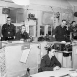 ROYAL AIR FORCE FIGHTER COMMAND, 1939-1945. (CH 1401) Interior of the Sector 'G' Operations Room at Duxford, Cambridgeshire.  The callsigns of fighter squadrons controlled by this Sector can be seen on the wall behind the operator sitting third from left.  The Controller is sitting fifth from the left, and on the extreme right, behind the Army Liaison Officer, are the R/T operators in direct touch with the aircraft. Copyright: © IWM. Original Source: http://www.iwm.org.uk/collections/item/object/205195667